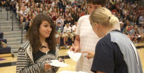 Student council sponsor Jessica DeWild hands out gift cards as prizes during freshman orientation.