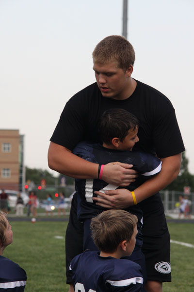 Senior Zach Callahan gives a hug to a future Jaguar football player. Photo by Emily Johnson