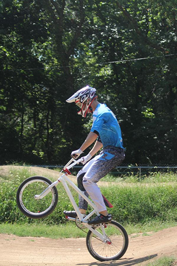 Senior Josh Thomason pops a wheelie while practicing riding his BMX bike on Sunday, Sept. 8 in Topeka. He is preparing to compete in the Grand Nationals.