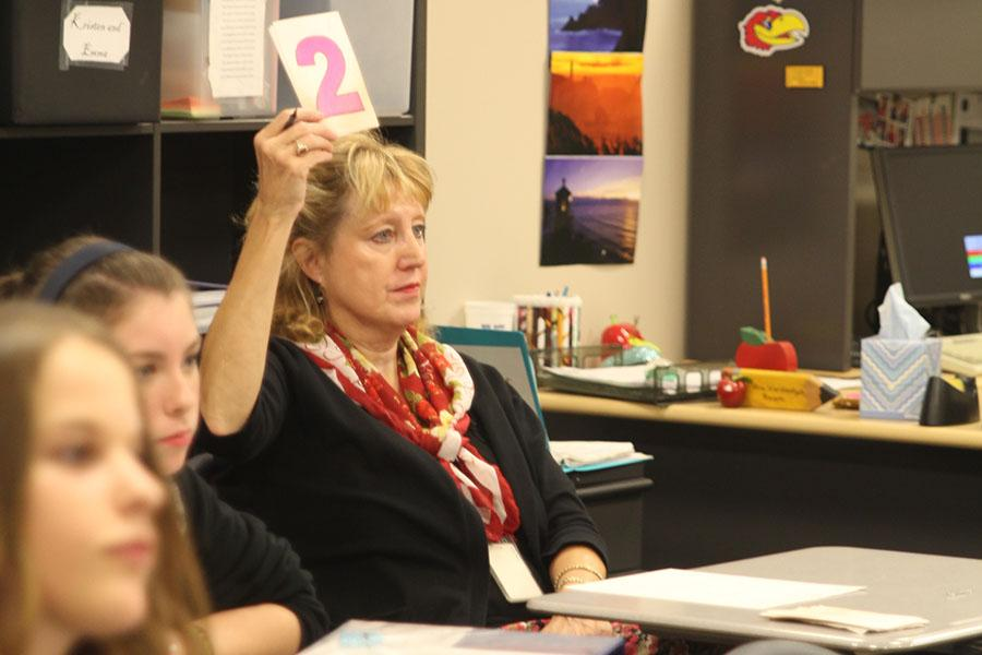 Debate+teacher+%0AJeanette+Hardesty+holds+up+a+time+card+while+her+students+practice+for+their++meet+at+Olathe+North+High+School+on+Saturday%2C+Oct.+26.+%0APhoto+by+Halie+Rust