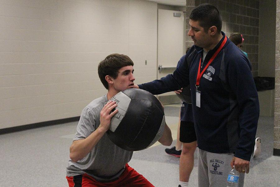 Motivating+senior+Bobby+Hellon%2C+fitness+teacher+Travis+Keal+leads+a+medicine+ball+workout+during+a+lifetime+fitness+class+on+Monday%2C+Nov.+11.+Keal+was+recently+nominated+as+the+October+Teacher+of+the+Month+due+to+his+inspiring+words+and+support+for+his+students.