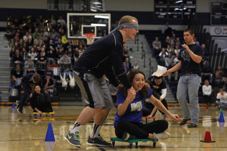 Junior+Mitch+Perkins+and+junior+Logan+Marney+participate+in+a+blindfolded+race+on+scooters+against+the+freshman%2C+sophomore%2C+and+senior+classes+at+the+winter+homecoming+pep+assembly+on+Friday%2C+Jan.+17.