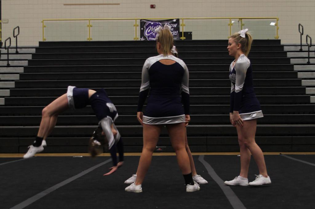 Senior+Taylor+Schmidt+does+a+back+handspring+into+the+arms+of+her+bases+during+her+individual+stunt+sequence.+The+individual+group+received+a+one+rating+at+the+Andover+Central+Showcase+on+saturday%2C+Feb.+15.+
