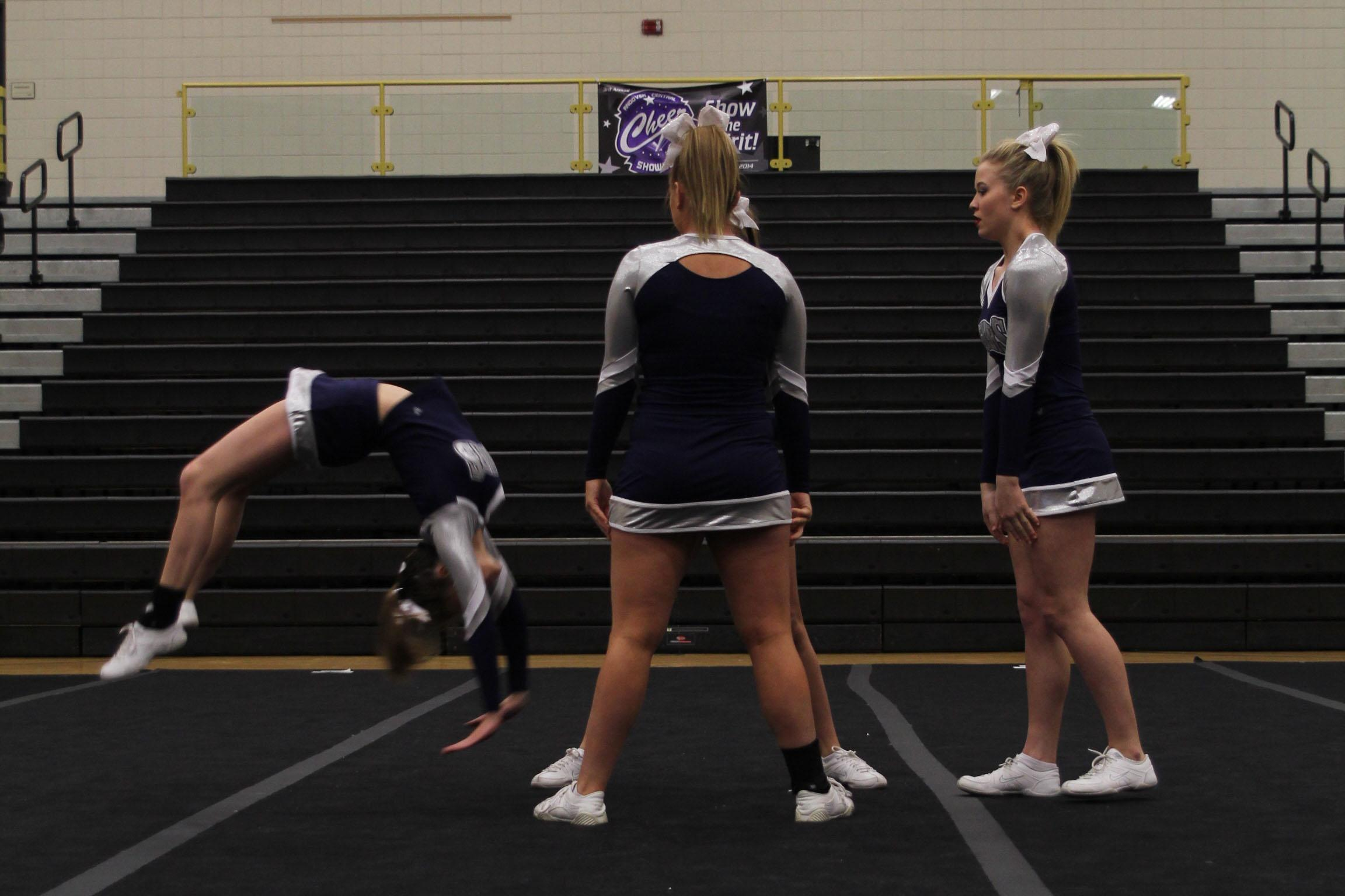 Senior Taylor Schmidt does a back handspring into the arms of her bases during her individual stunt sequence. The individual group received a one rating at the Andover Central Showcase on saturday, Feb. 15.