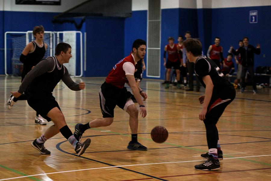 Sophomore Joe Wilson dribbles down the court while sophomores Brock Miles and Tyler Shurley defend during a recreation basketball game at Okun Fieldhouse on Thursday, Jan. 30.