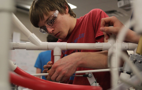 With the robotics build season winding down,  junior Kyal Long puts the finishing touches  on the team's robot on Thursday, Feb. 20.