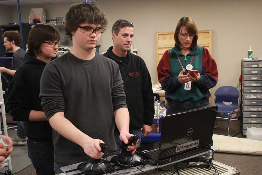 Sophomore+Rhett+Pierce+controls+the+robotics+team%27s+newest+robot+as+the+team+puts+on+the+final+touches+before+their+next+competition.