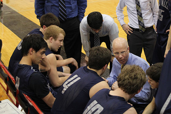 Former head boys basketball coach Justin Bogart discusses strategy with his players during a timeout on Friday, March 7.