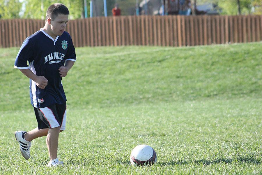 Preparing to kick the ball during a drill, Matthew Santaularia practices with the unified soccer team on Sunday, April 26.