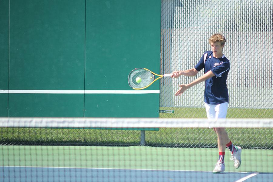 During the tennis dual on Thursday, April 30, sophomore Spencer Butterfield forehands the ball to his St. James Academy opponent.