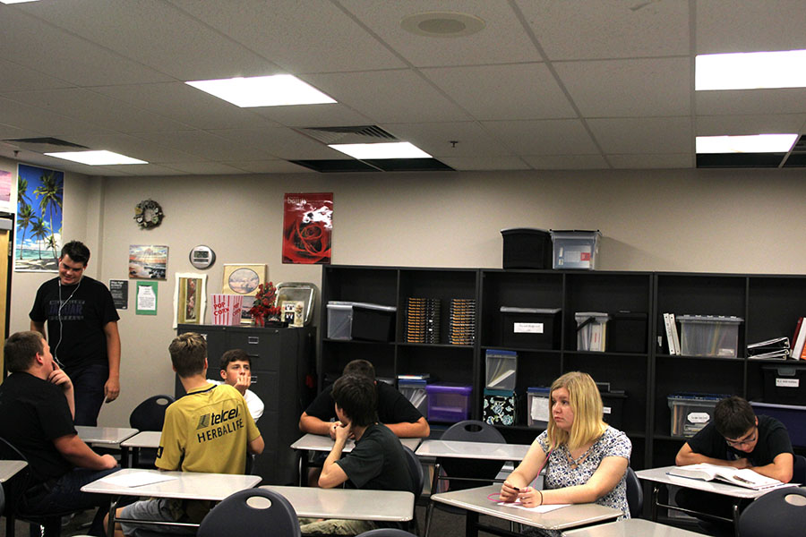 Students in Jeannette Hardesty's class look up at the holes in her room, but continue normal seminar activities despite the damage in the ceiling.