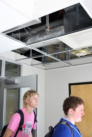 Senior Hunter Paxton and junior Shane Howell walk out the library entrance doors despite the gaping hole in the ceiling.