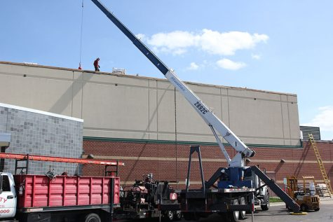 Workers continue to work on the roof during the school day.