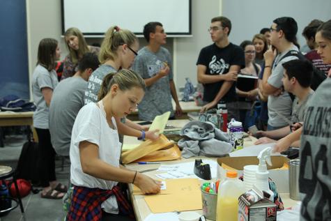 Junior Jordan Robinson works on placing t-shirt designs into the folders.