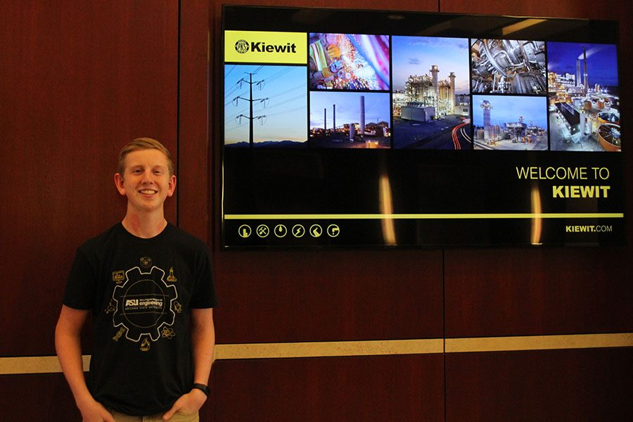 Junior Landon Butler stands in front of a slideshow at Kiewit Engineering and Design on Thursday, Oct. 20.
