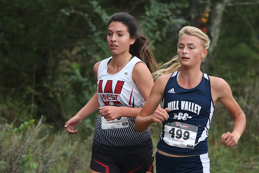 Running+alongside+her+competitor%2C+junior+Bella+Hadden+races+during+the+Eastern+Kansas+League+meet+on+Thursday%2C+Oct.+13.+%22I+feel+like+the+team+overall+did+well+for+our+first+year+in+the+EKL%2C%22+Hadden+said.+%22Our+main+goal+was+to+beat+BVSW+and+we+edged+them+out+by+two+points.%22