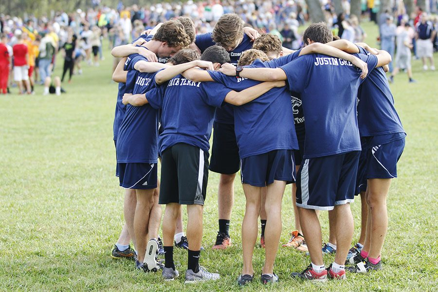 Huddling+before+their+race%2C+the+boys+team+prepares+to+run+the+course+at+Rim+Rock+Farms.