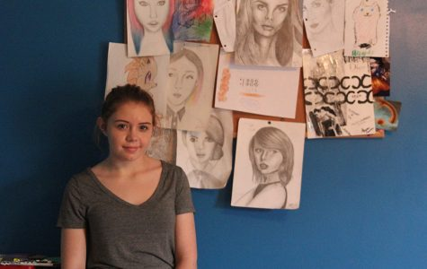 Standing beside her artwork, freshman Shaina Isaacsen poses on Saturday, Oct. 30.