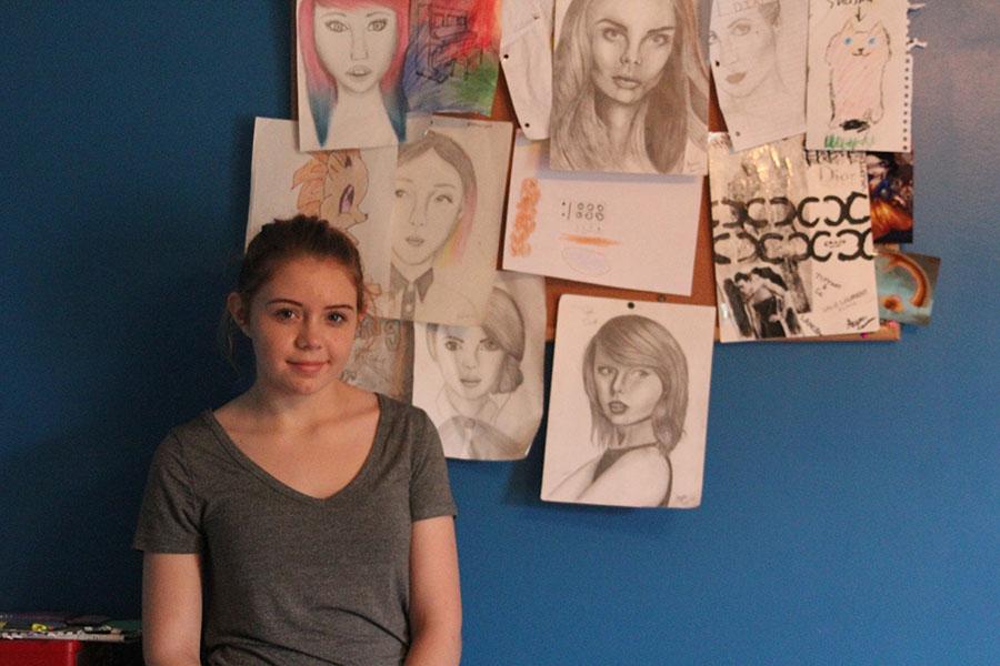 Standing beside her artwork, freshman Shaina Isaacsen poses on Saturday, Oct. 30.