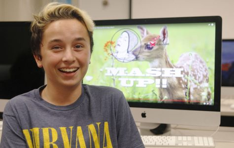 With a video from his YouTube channel pulled up in the background on Tuesday, Oct. 18, freshman Aidan Thomas smiles in journalism teacher Dorothy Swafford's classroom.