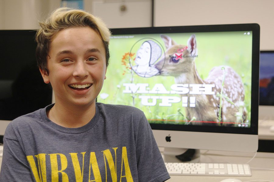 With+a+video+from+his+YouTube+channel+pulled+up+in+the+background+on+Tuesday%2C+Oct.+18%2C+freshman+Aidan+Thomas+smiles+in+journalism+teacher+Dorothy+Swafford%27s+classroom.+%22I+like+%5BYouTube%5D+because+I+can+share+my+videos%2C%22+Thomas+said.+%22Even+if+nobody+watches+them%2C+I+can+still+post+them+and+I+feel+good+that+some+people+will+%5Bget+to%5D+experience+my+content.%22
