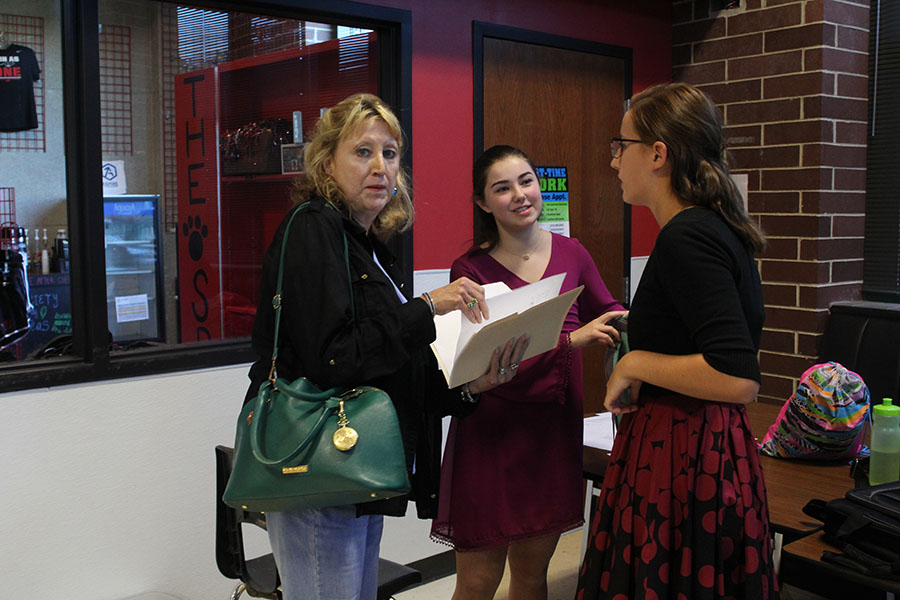 Two debate team members converse with their sponsor, Jeanette Hardesty.
