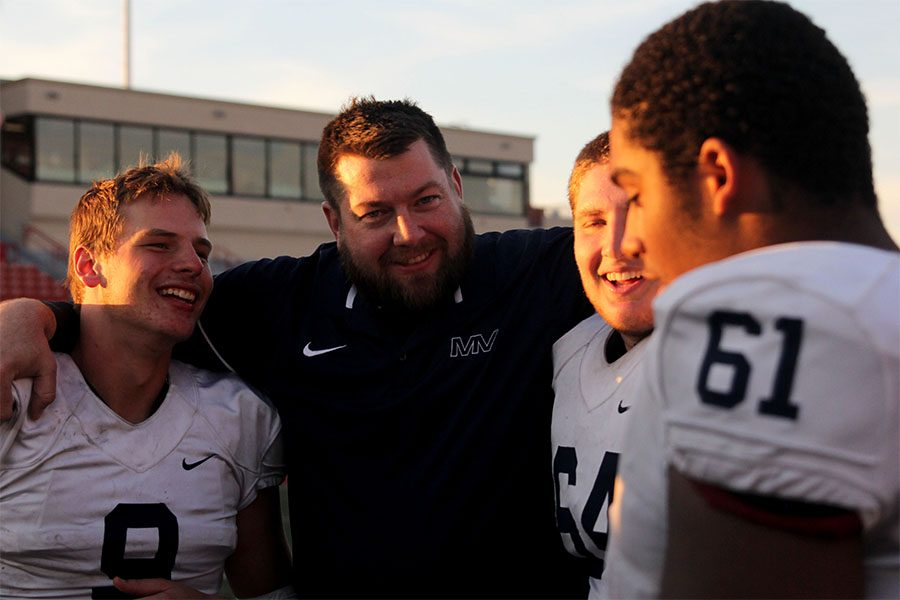 Coach Alex Houlton laughs with junior Brody Flaming and senior Jacob Campbell.