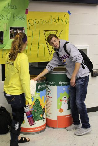 Junior Trent Anderson places coat in the bin on Monday, Nov. 7