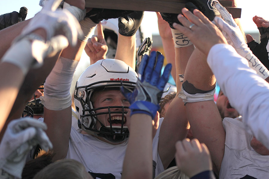 Senior Cole Ivey looks up at the state championship trophy as he holds it.