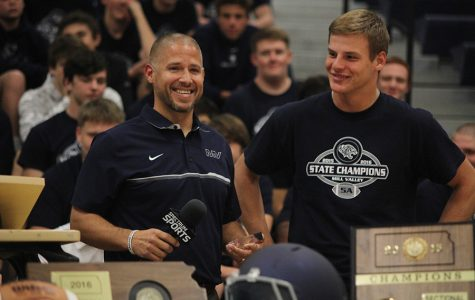 At the pep assembly on Tuesday, Nov. 29, head football coach Joel Applebee helps award junior Brody Flaming as Student Athlete of the Week.