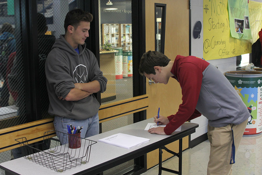 Before heading to class, senior Adam Gillette fills out one of the new department of the month forms on Wednesday, Nov. 9.