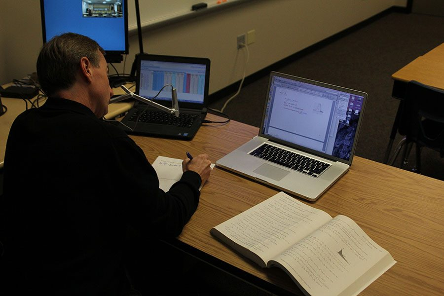 Math+teacher+Brian+Rodkey+uses+a+web+cam+to+broadcast+his+notes+to+both+students+in+his+classroom+and+to+students+at+DHS.