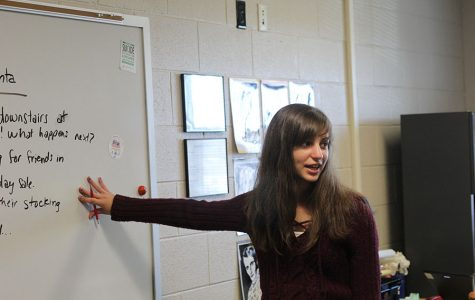 While pointing at the board during a creative writing meeting, sophomore Sarah Gawith explains the holiday writing activity.