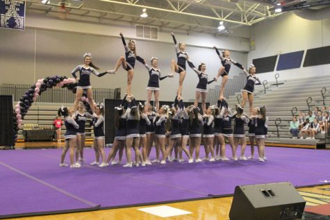The cheer team completes a large stunt using all of the cheerleaders on the team.