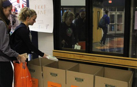 Sophomores Grace Goetsch and Sophie Friesen place their books in the box for donation.
