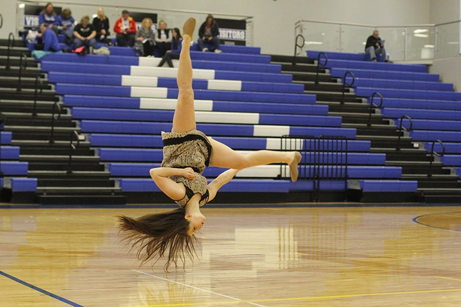 Sophomore Olivia Augustine flips during her solo.