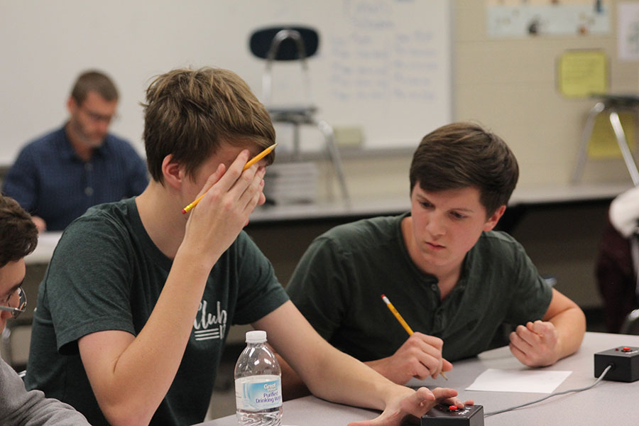 Juniors Jarod Griggs and Sam Phipps work out the answer of the math problem at the Turner tournament on Thursday, Dec. 8.