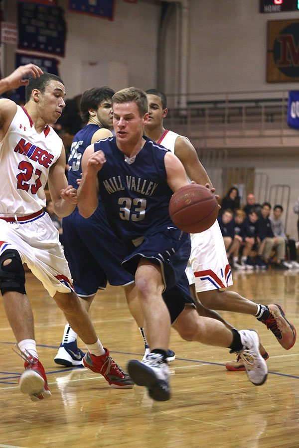 While pushing past a Bishop Miege player, junior Brody Flaming looks to score.