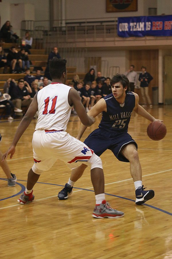 While dribbling the ball, junior Ike Valencia takes on an opponent.