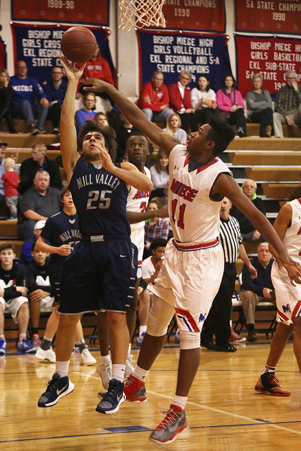 Junior Ike Valencia goes up for a shot against a Bishop Miege player.
