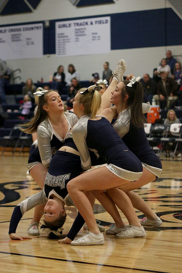 Cheerleaders prepare for a stunt during their halftime performance.
