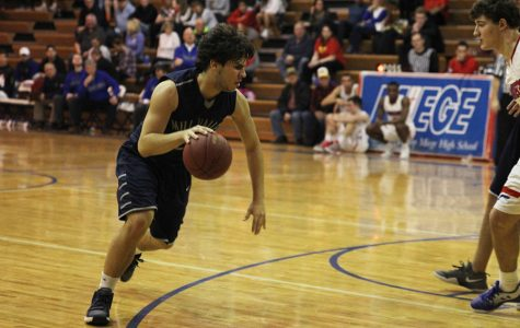 Junior Ike Valencia dribbles down the court at the boys basketball game on Wednesday, Jan. 25.