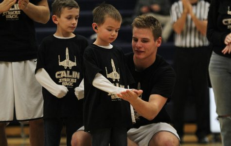 After the Make-A-Wish club's speech prior to the game on Friday, Jan. 27, junior Brody Flaming high-fives Calin Strahm.