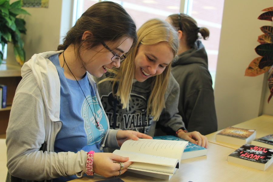 While+looking+at+one+of+the+books+available+for+review%2C+freshman+Callie+Roberts+and+freshman+Joan+Downey+laugh+in+the+library+on+Wednesday%2C+Jan.+25.
