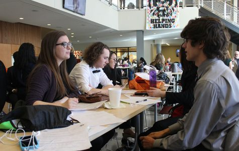 Along with senior Sydney Williamson, juniors Parker Johnson (middle) and Zoltan Gothard (right) prepare their competition pieces in the Lansing High School commons on Saturday, Jan. 28.