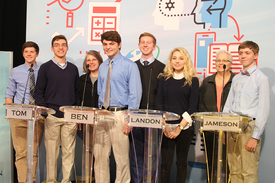 Posing for pictures, the Quiz Bowl team stands tall. From left to right: junior Sam Phipps, senior Tom McClain, coach Mary Beth Mattingly, senior Ben Stadler, junior Landon Butler, senior Emma Wilhoit, coach Donna Riss and junior Jameson Isaacsen.
