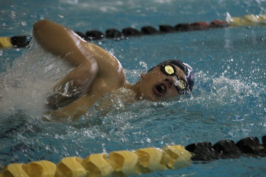 As he goes up for a breath, junior Noah Kemper competes in the 200 yard freestyle race.