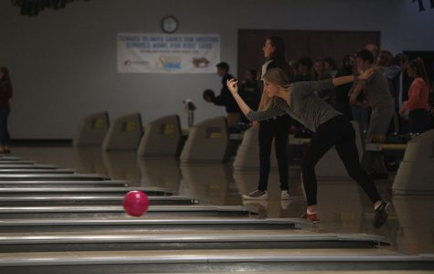 Focusing on her bowling form, junior Bella Hadden, watches the ball roll down the lane.