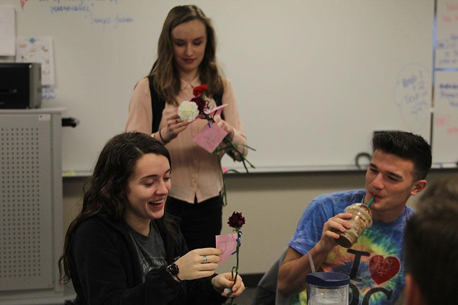 Senior Savannah Chappell smiles as she is given a carnation by NEHS member sophomore Liz Fraka.