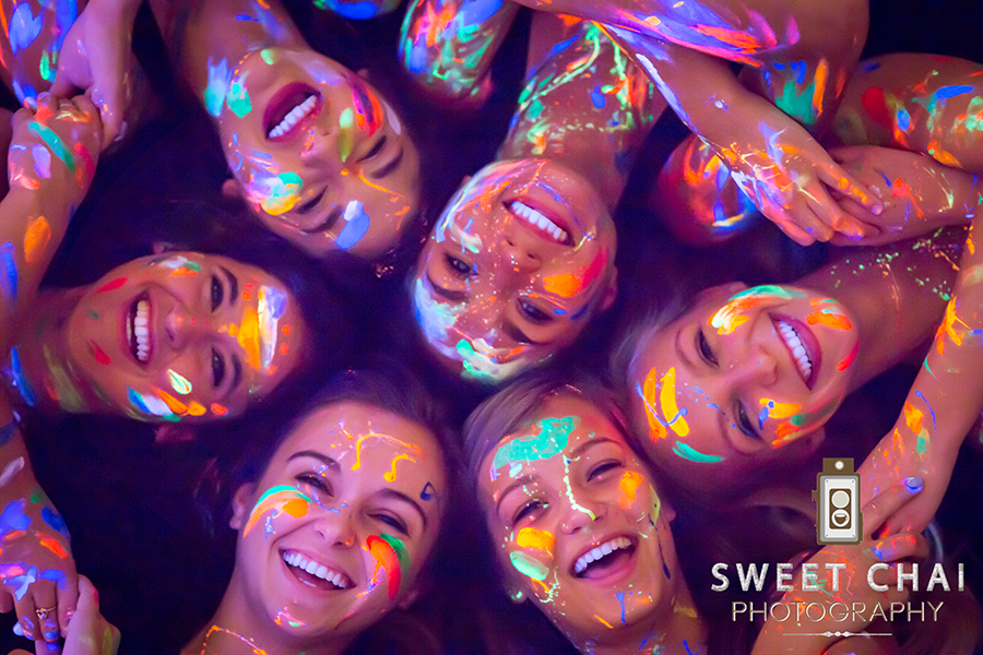 Senior Sweet Chai models add unique elements to their photoshoot using a blacklight effect.